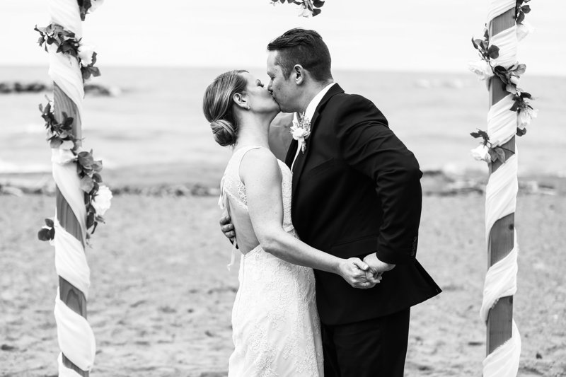 Bride and groom share first kiss at their Presque Isle beach wedding