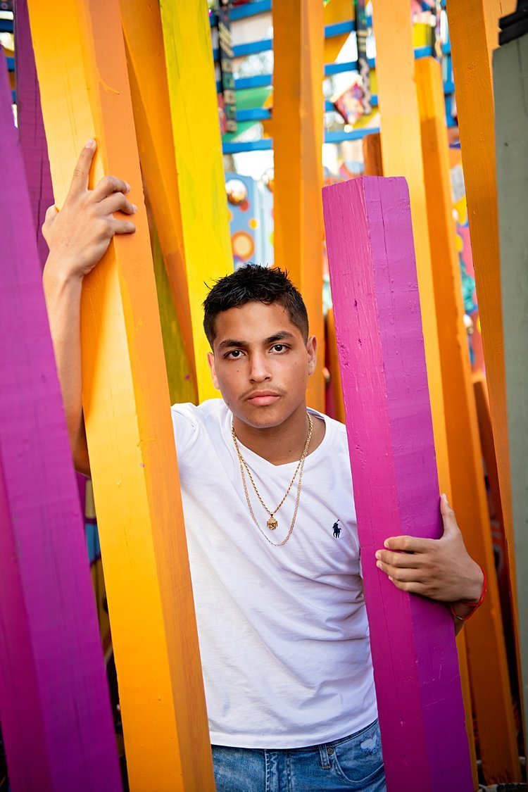 High school senior boy in white Polo tee standing among pink, orang and yellow wooden posts at Randyland in Pittsburgh, PA