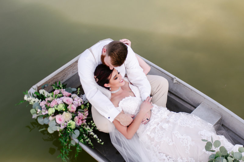 bride and groom laying in row boat in lake with flowers