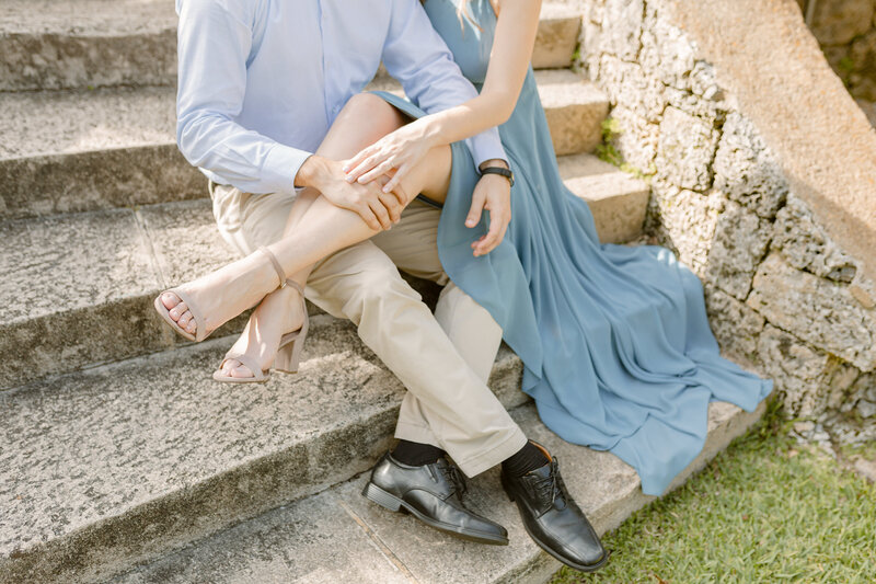 Man and woman sit next to each other on stone steps outdoors with woman's legs over man's legs during engagement photography session