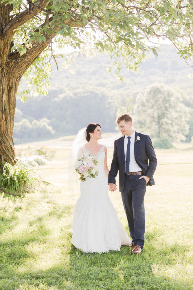bride and groom walking under tree at springfield manor winery and distillery wedding by costola photography