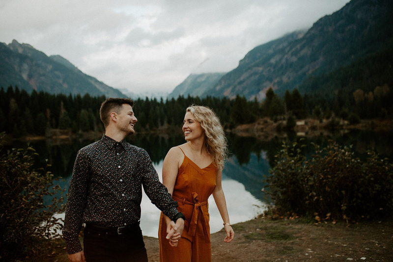 Couple holding hands smiling at each other during their Washington mountain engagement session