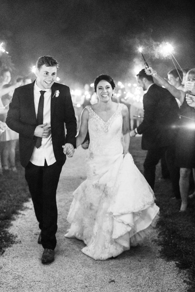 bride and groom running sparkler exit at springfield manor winery and distillery wedding by costola photography