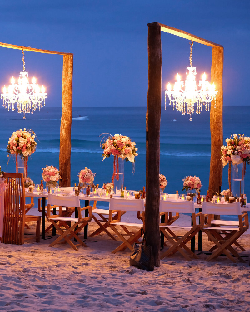 A wedding or party table is set on a beach at dusk with chandeliers hanging from wooden frames over the pink flowers.