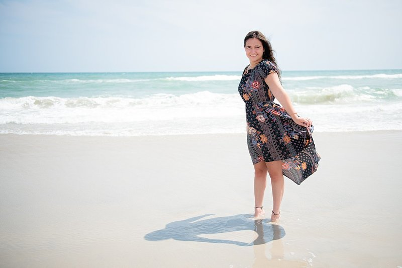 High school senior girl in black floral dress standing tiptoe on windy beach with dress flowing and wave crashing in the background