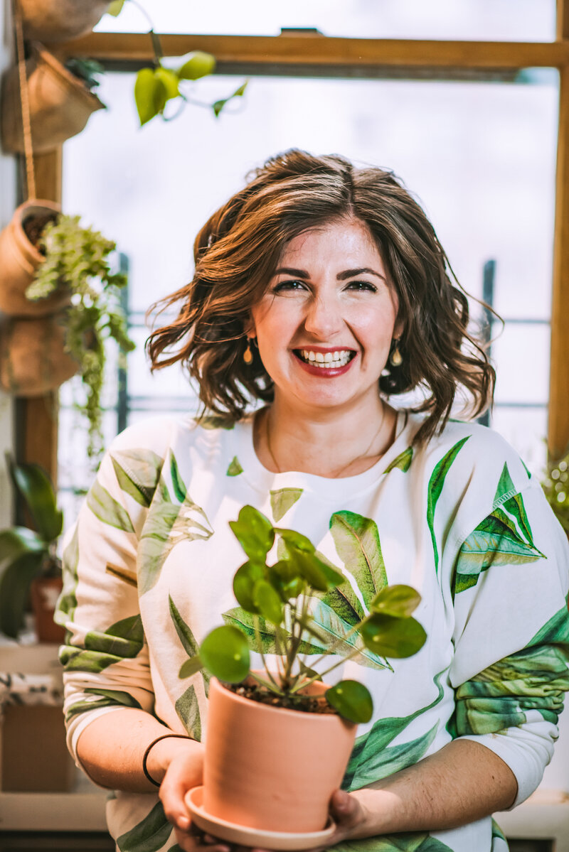 Bloom & Grow Radio podcast host, Maria Failla, smiles brightly while holding a plant and wearing a plant printed sweatshirt