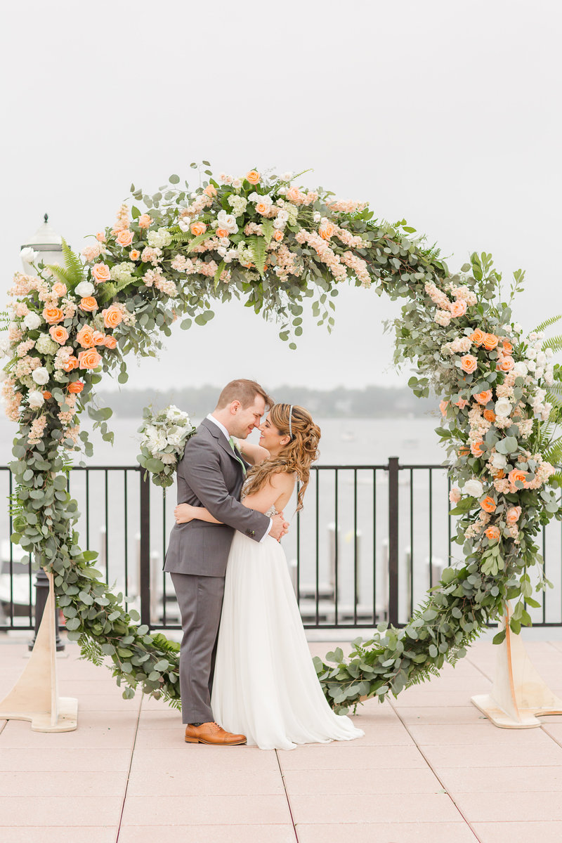 Bride and groom with giant floral wreath