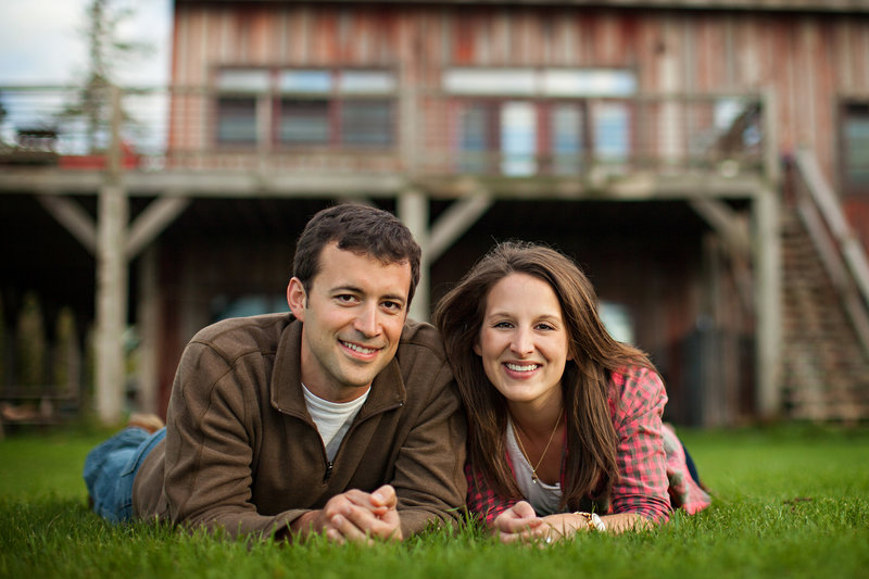 Engaged couple laying on lawn with barn venue in the background.
