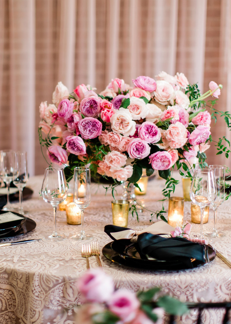 Elaborate pink peony and pink rose centerpiece on table with multiple black table settings and glases
