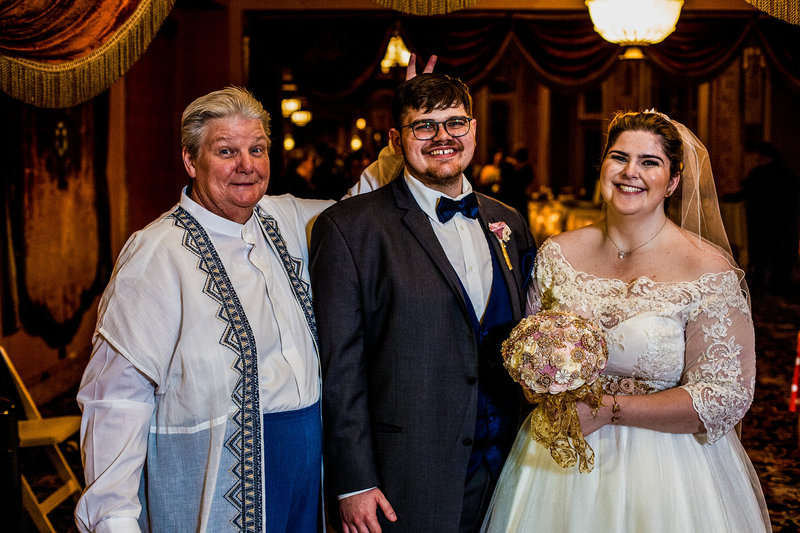 Bride and groom pose with officiant at the end of their Warner Theatre wedding ceremony