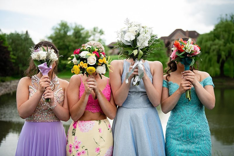 High school senior girls before Prom holding floral bouquets in front of their faces