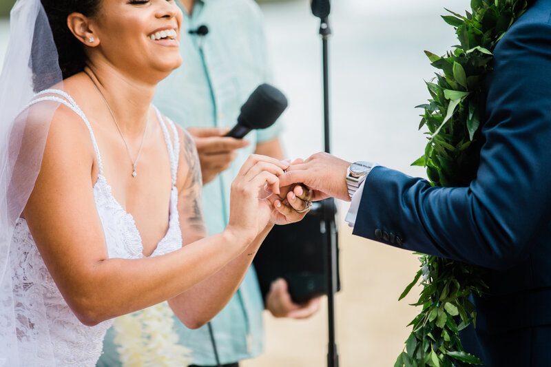 bride and groom exchanging rings at kualoa ranch