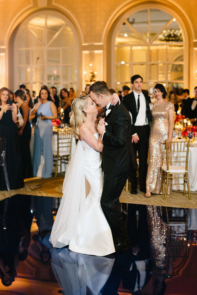 Bride and groom dancing on ballroom while guests watch at wedding reception