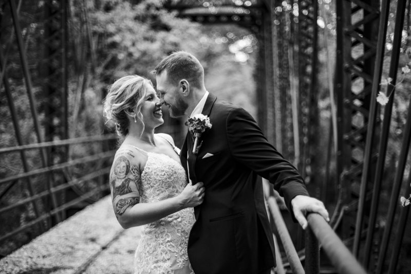 Bride and groom laughing on train trestle at Barn at Conneaut Creek