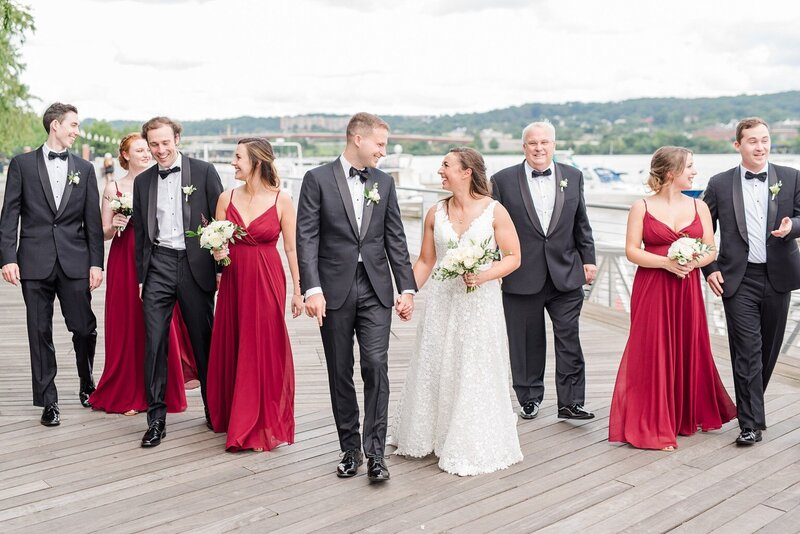 Bride with small bouquet and wedding party on waterfront pier in Washington DC