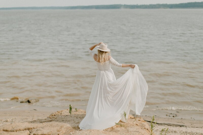 bride holding her hat and dress on beach