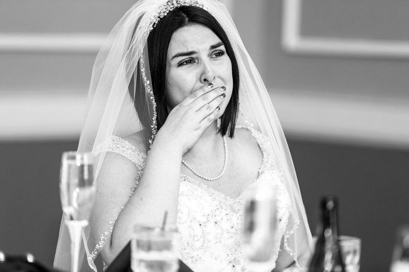 bride covering her mouth and fighting back tears at her wedding reception in Pittsburgh, PA