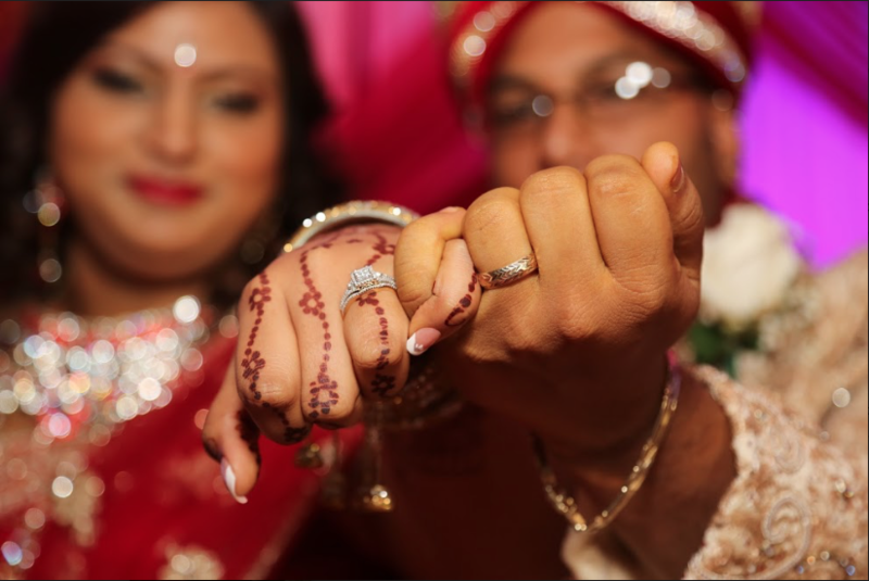 Bride's and Groom's linked hands showing off wedding rings. Photo by Ross Photography, Trinidad, W.I..