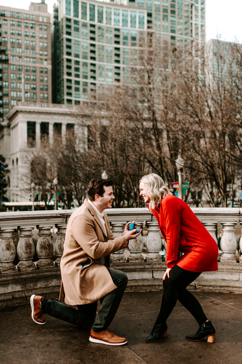 man on one knee proposing to woman in a red coat