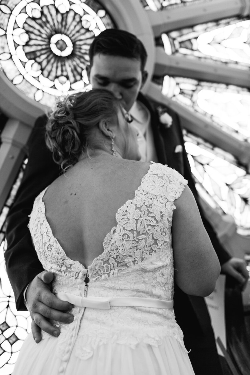 bride and groom embrace in front of old stained glass window in ohio