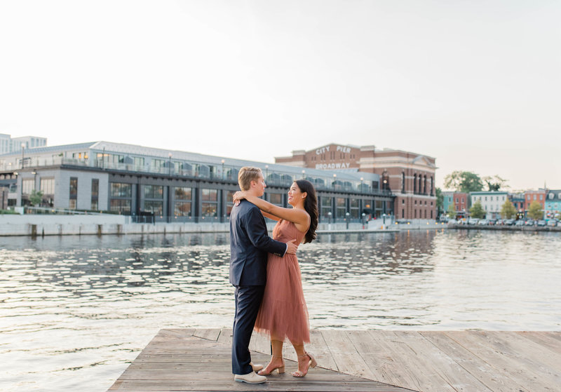 Engagement session bride and groom dance near the water in Baltimore
