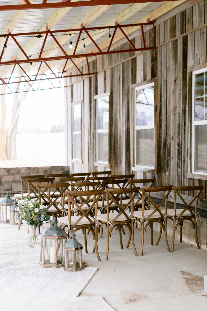Rustic chairs set up for the ceremony with off white rugs as the ail runner.