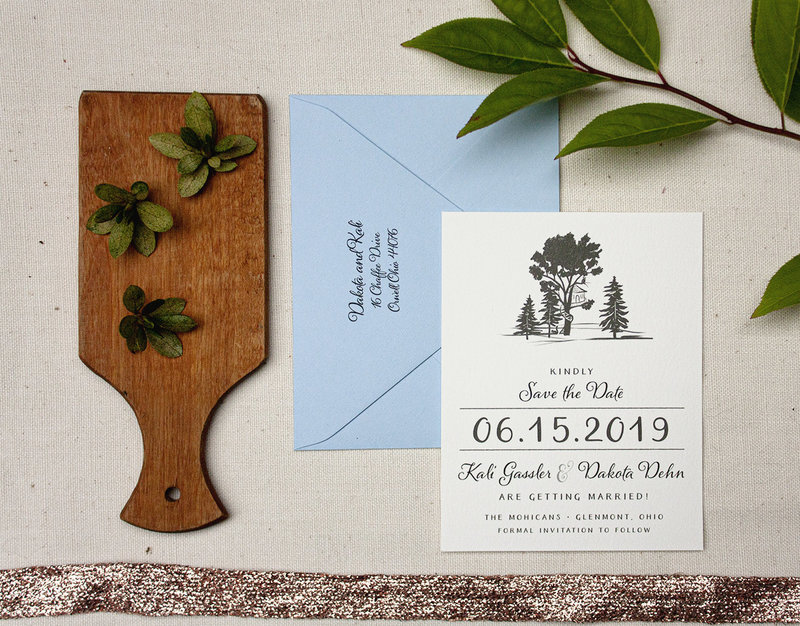 Save the Date with a simple illustrated silhouette of trees and a treehouse.