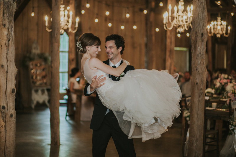 A groom lifts and swings his bride around during their first dance at Meadow Hill Barn in Columbia, Tennessee.