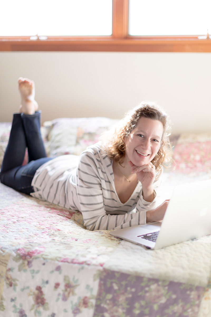 business owner lays on bed with laptop and smiles for branding picture