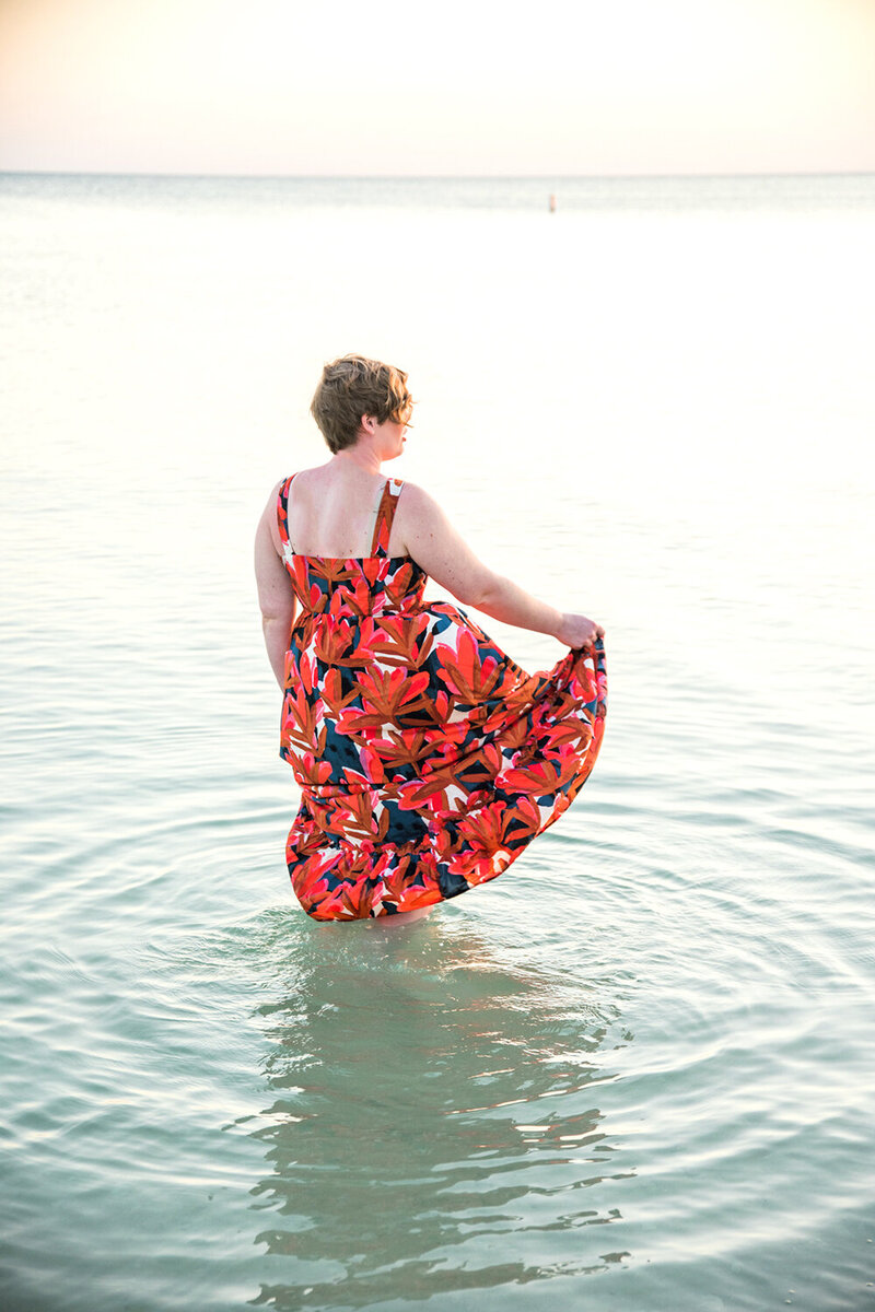 Woman walking in the ocean in a red dress