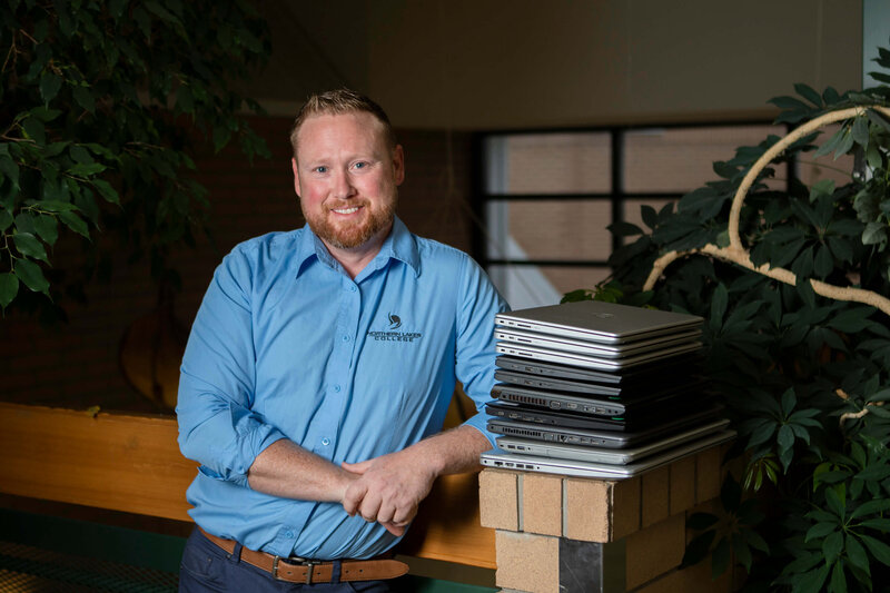 computer technician stands by a stack of laptops