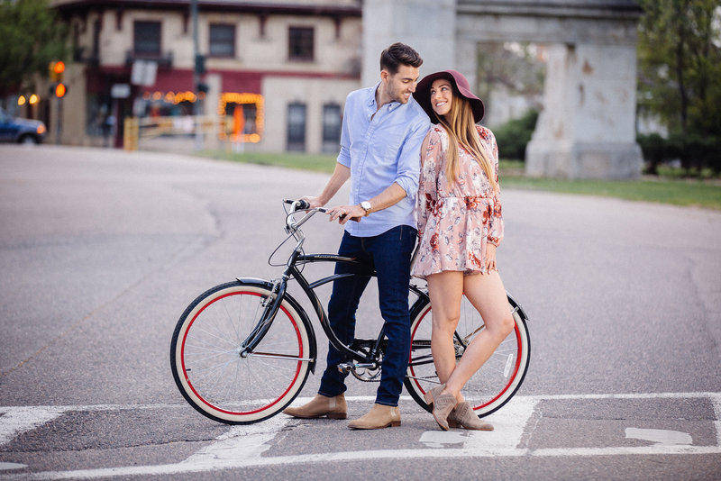An engaged couple smile at each other while sitting on a bicycle.