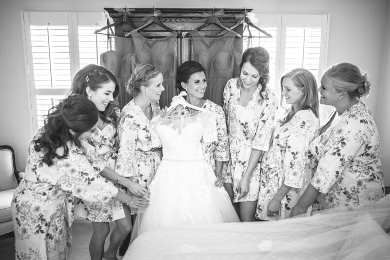 A bride is showing her wedding dress to her bridesmaids.
