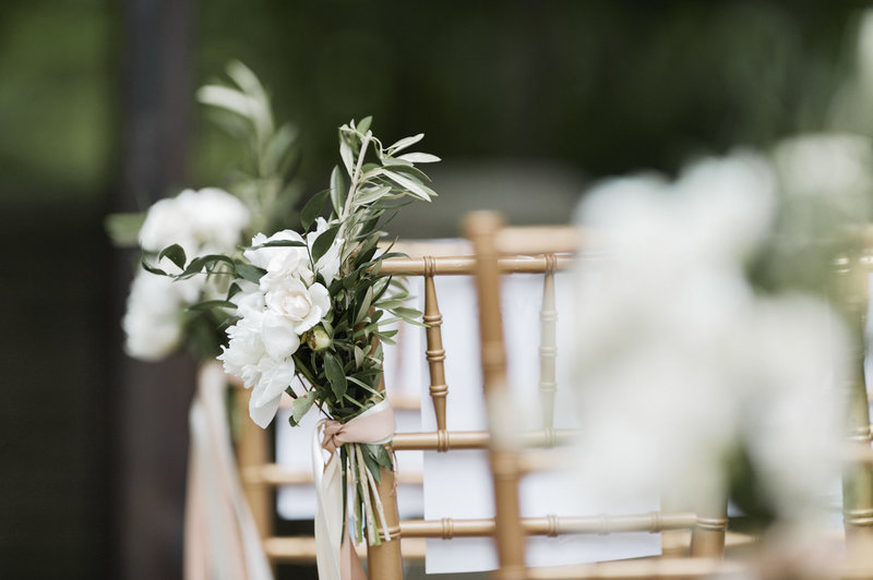 White flowers with olive leaves aisle decor