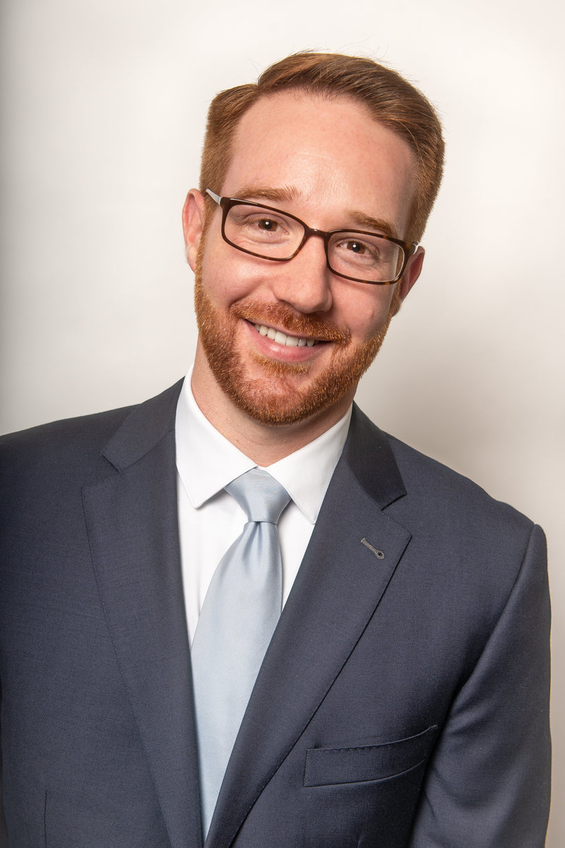 Red haired young business man smiles for headshot in studio