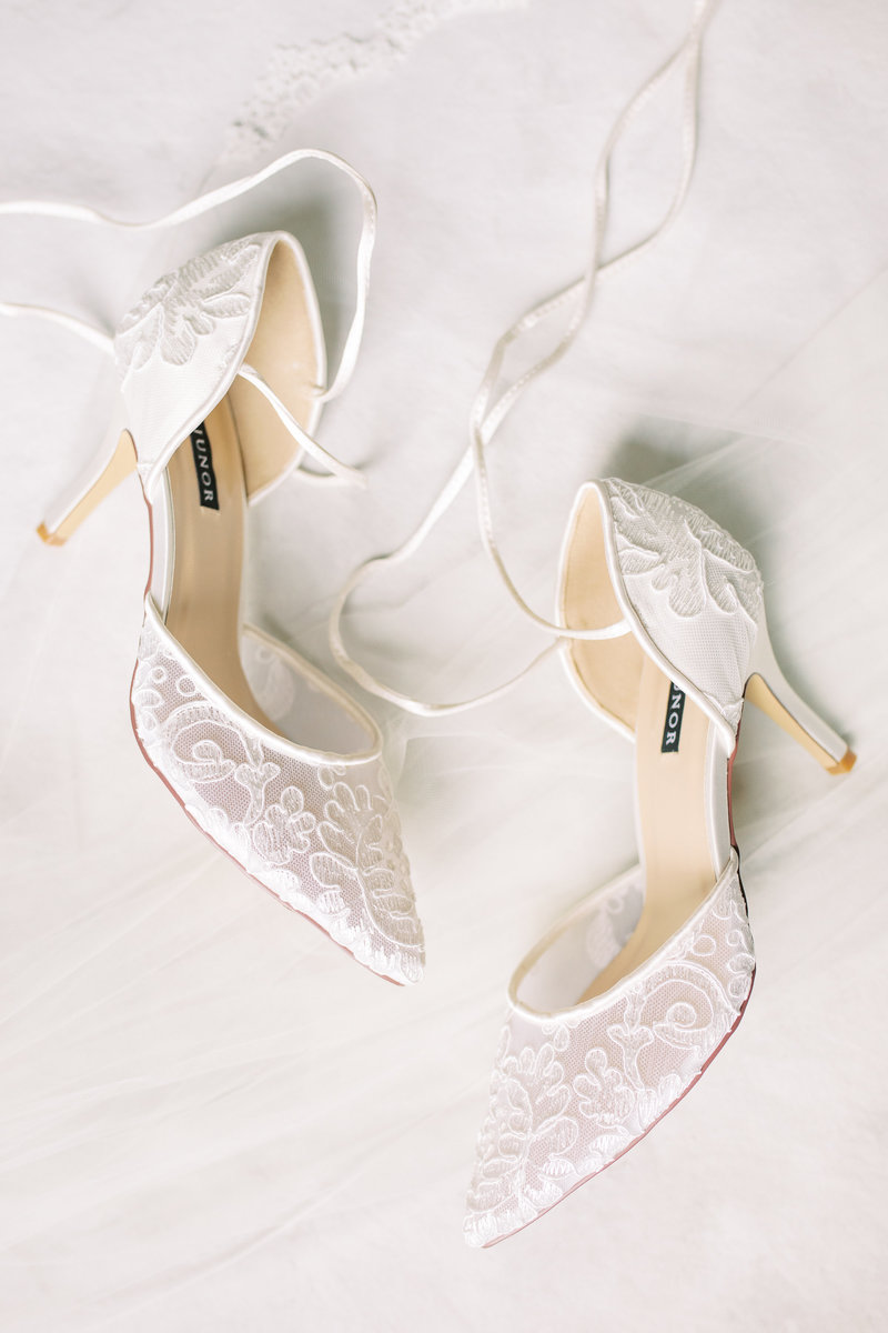 Detail shot of lace ivory wedding shoes on a neutral ivory background