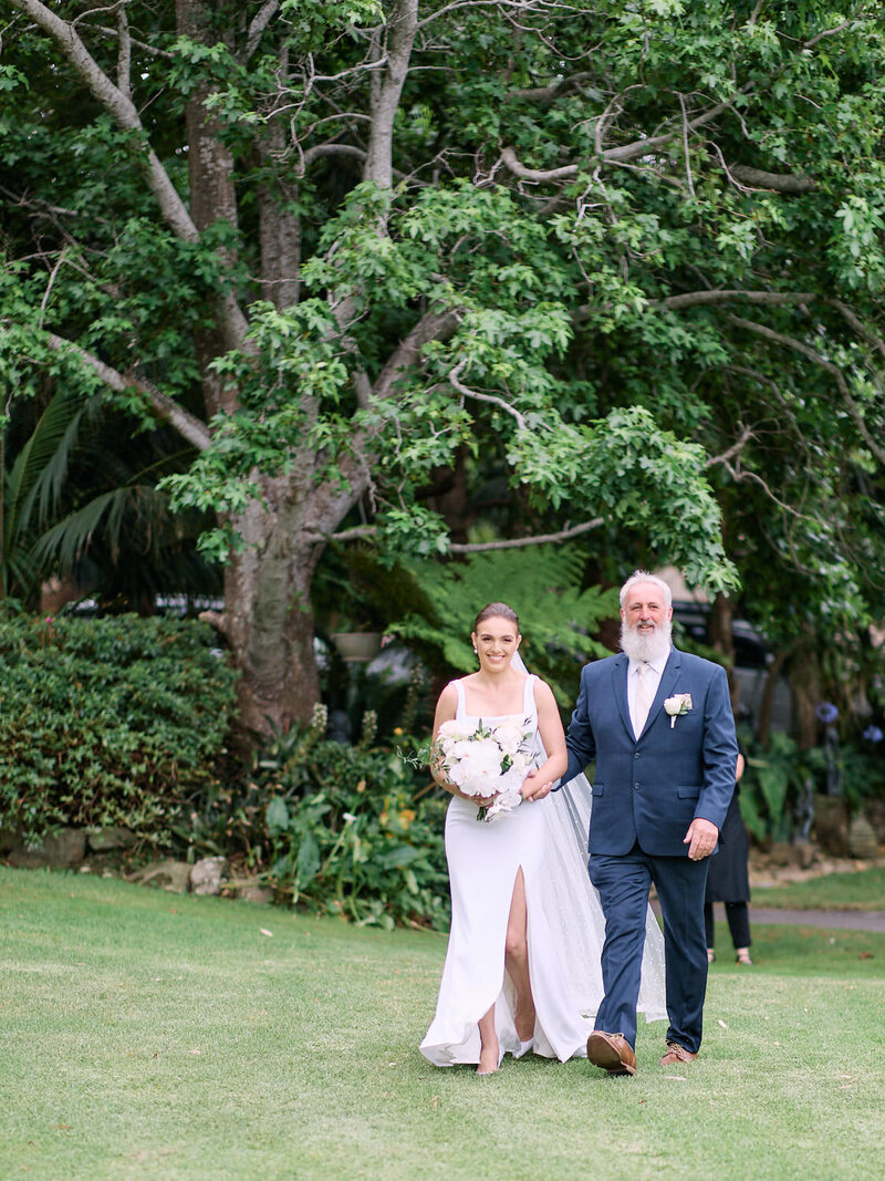 Father of the bride walking daughter across lawn to ceremony at Tumbling Waters Retreat
