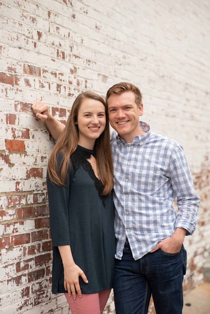 Young couple leaning against white-painted brick wall