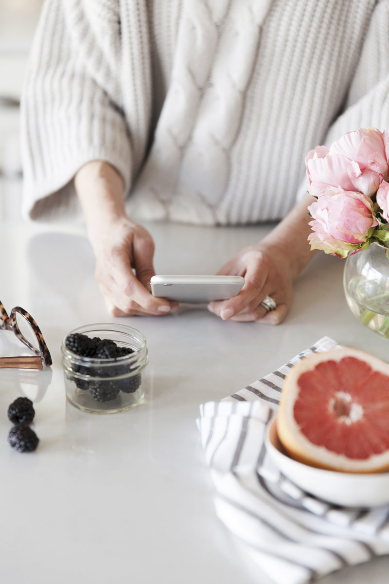 Lady holding iPhone at kitchen counter with flowers