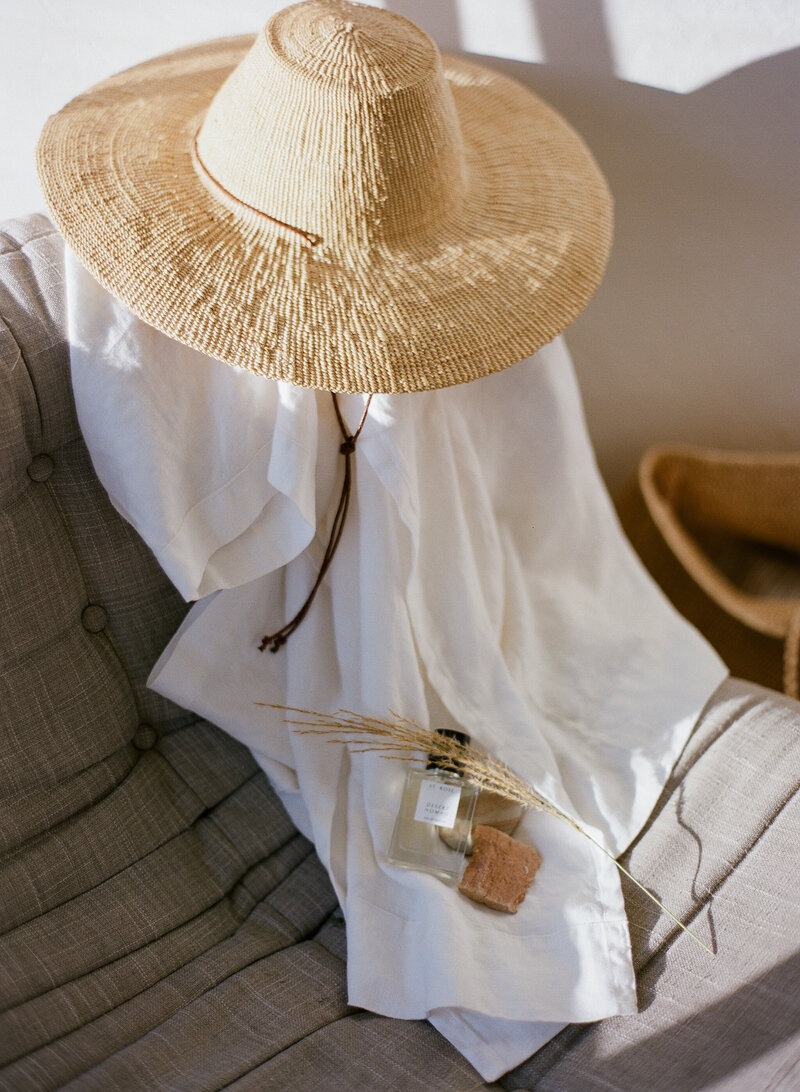 sun hat draped across white linen top on chair
