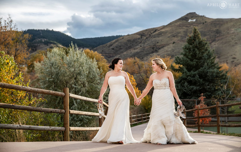 Two brides walk down the path with their shoes off at The Golden Hotel