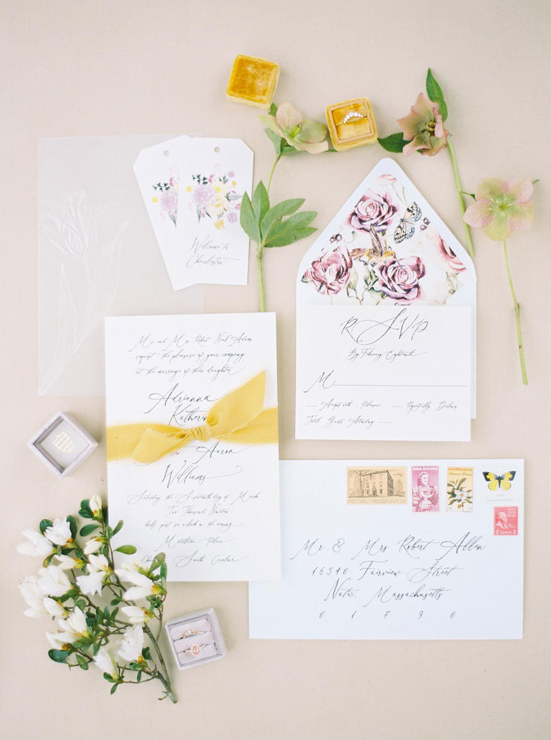 Wedding stationery flatlay with yellow ribbons