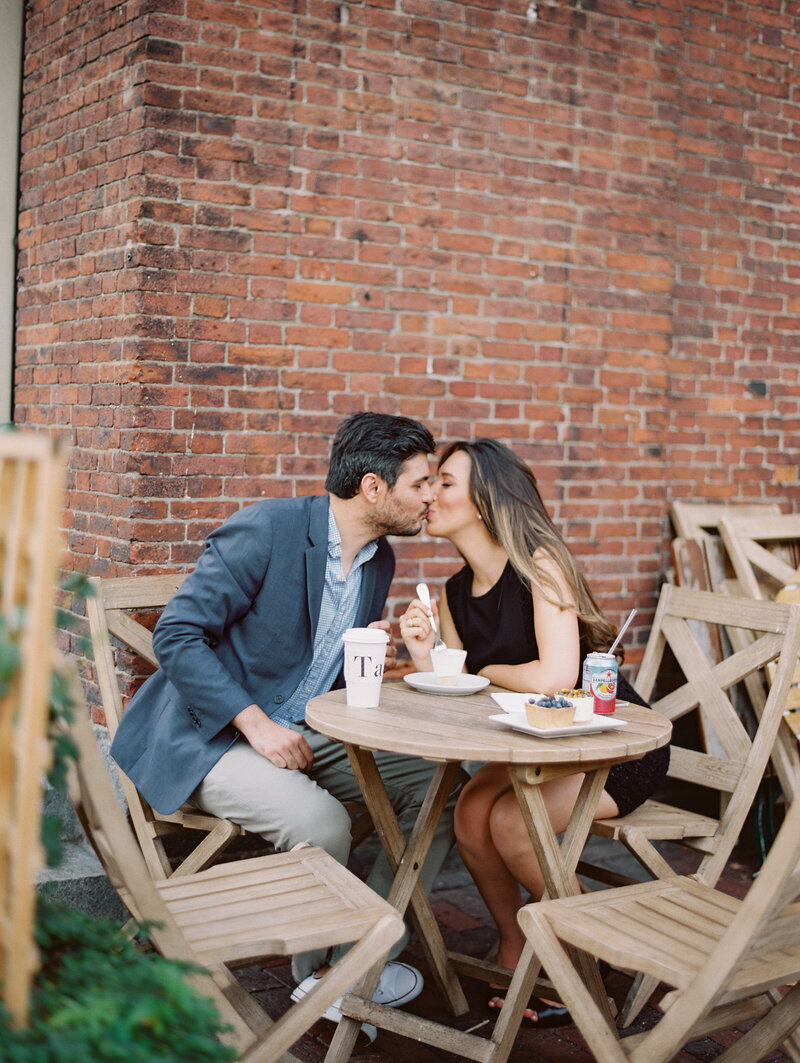 Couple kisses will eating dessert at Boston engagement session
