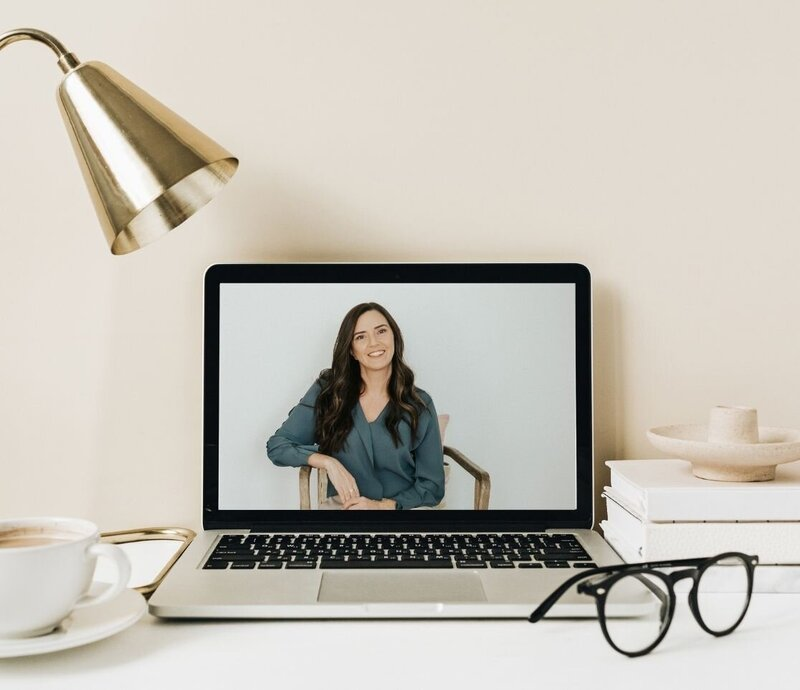 A laptop rests on a desk next books, a lamp, glasses, and a cup of coffee. On the screen, Idit Sharoni smiles as she sits in a chair. Her practice offers online therapy in Florida, online relationship therapy, and other services. Contact us today for support through a teletherapy platform.