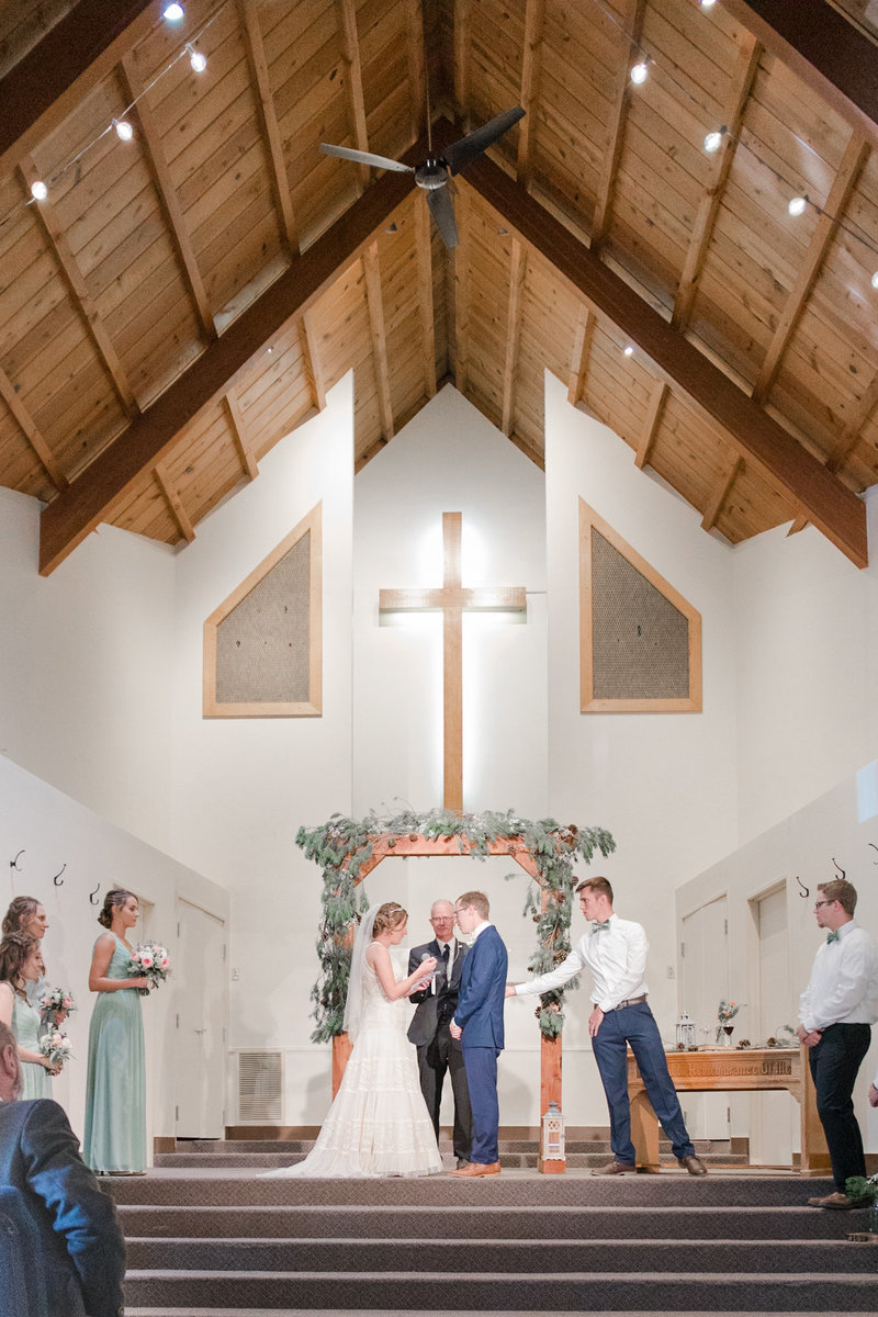 A groom and bride standing at an alter in the desert surrounded by family and friends