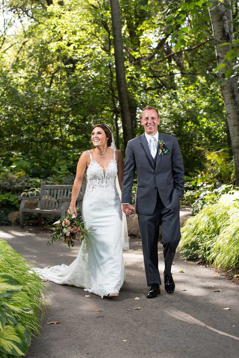 bride and groom walking at the green bay botanical gardens