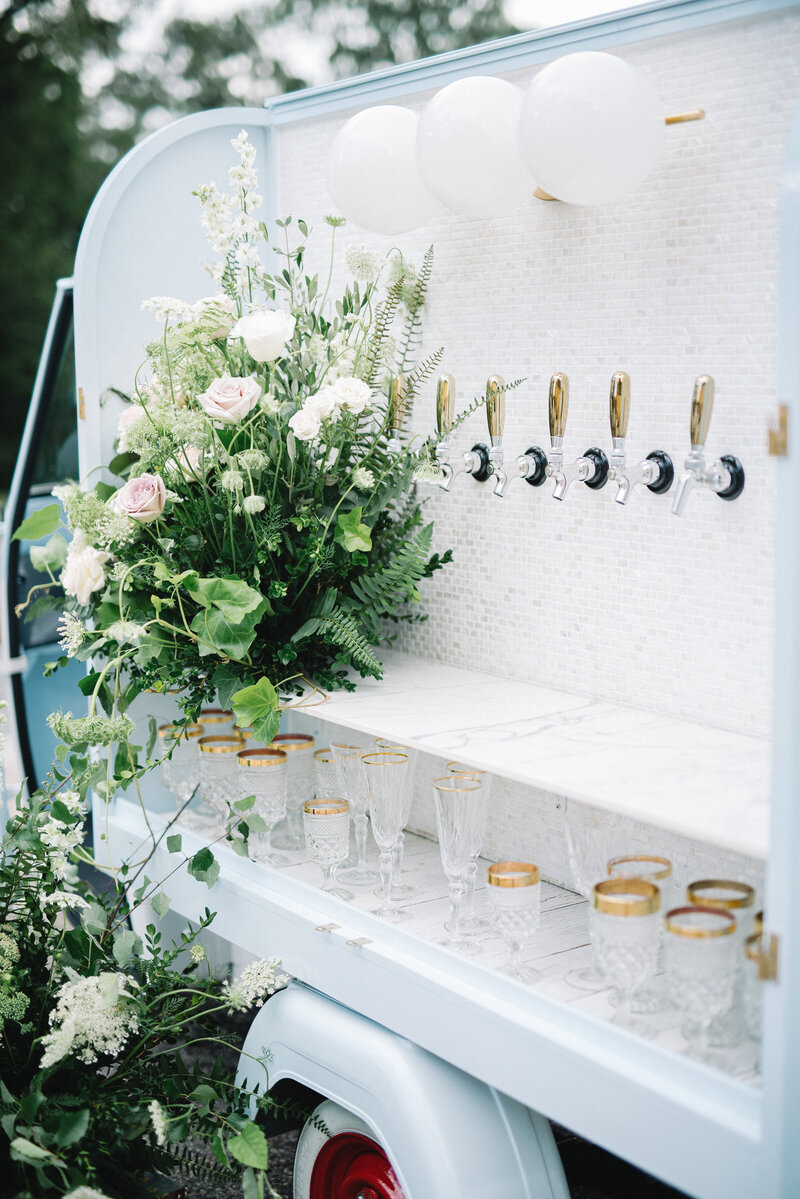 Tippy Tap Co. mobile bar at wedding with floral arrangements
