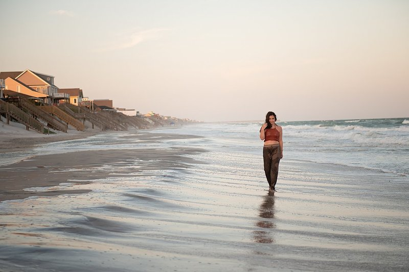 High school senior girl in harem pants and crochet crop top walking along water soaked beach at sunset