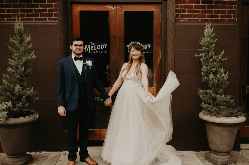 Bride swirls wedding gown skirt while holding hands and smiling with her groom in front of The Melody in Portland, Oregon