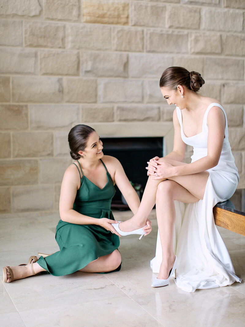 Maid of honour putting brides wedding shoes on during bride preparation